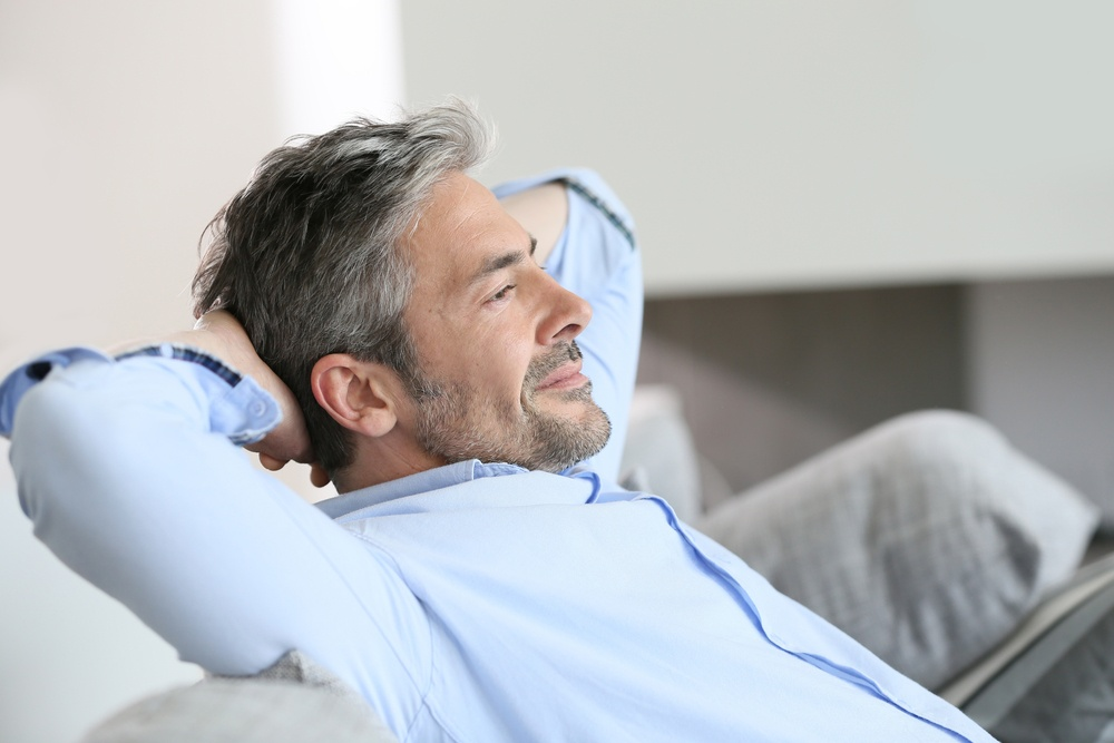 Middle-aged man having a restful moment relaxing in sofa.jpeg